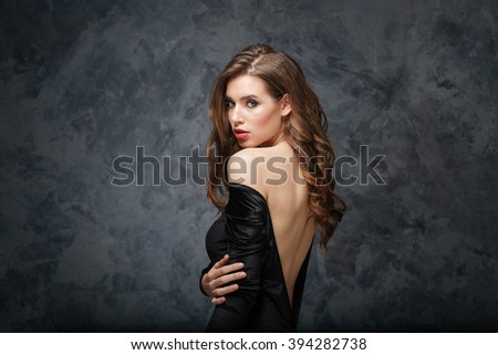 Sensual attractive young woman in classical dress with open back over grey background - stock photo
