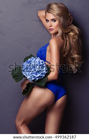Sensual beautiful blonde woman posing with flower. Girl with long curly hair.
