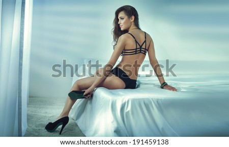 Sensual beautiful brunette woman sitting on big white bed, posing in sexy lingerie, looking away. Girl with slim body and long curly hair. - stock photo