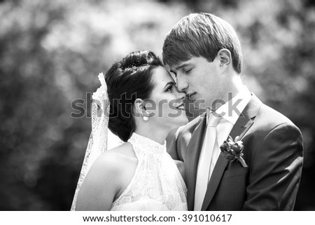 Sensual, beautiful couple of newlyweds hugging in floral meadow closeup