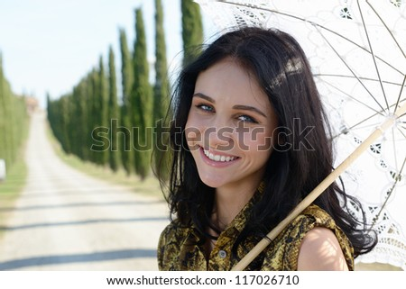 Sensual beautiful girl with white umbrella smiles on the background of cypress alley on sunny day - stock photo