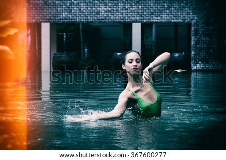 Sensual beautiful woman portrait wearing green swimsuit relaxing in swimming pool. Digital manipulation to simulate analogic film effect.