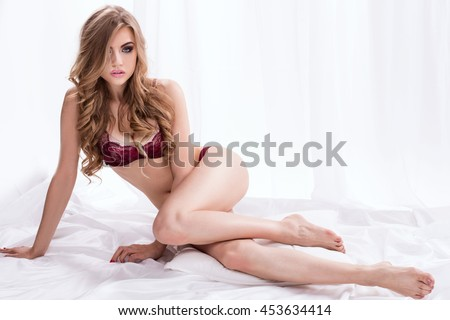 Sensual beautiful woman posing in elegant lingerie, lying in big white bed, relaxing. Perfect body. Long curly blonde hair. Glamour makeup. Bedroom. Romantic. - stock photo