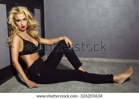 Sensual beautiful woman with long curly hair posing in studio, looking at camera. Elegant lady. - stock photo