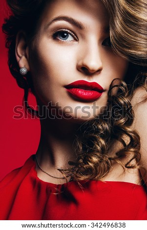 sensual beautiful woman with red lips and curly hair on red background