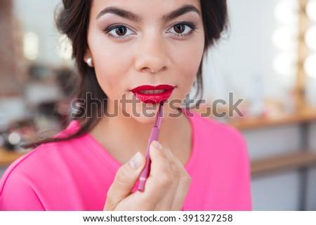 Sensual beautiful young woman applying red lipstick to her lips using lip brush - stock photo