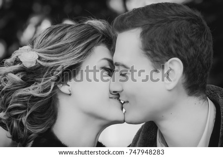 Sensual black and white portrait of happy kissing couple closeup - loving, newlyweds. Selective focus.