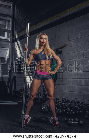 Sensual blond fitness model posing with barbell in a studio over gray background.