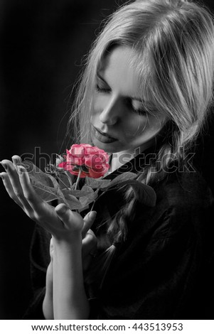 sensual blond girl with pink rose on black background