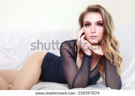 sensual blond woman in lingerie lying on a sofa - stock photo
