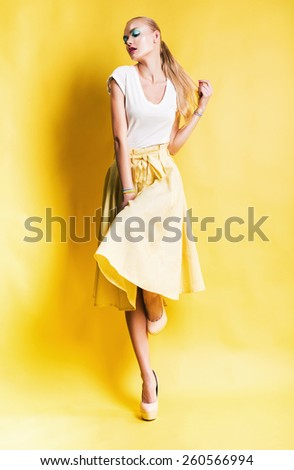 sensual blond woman in long yellow skirt on yellow background - stock photo