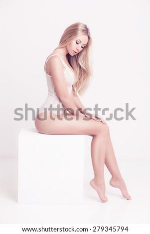 Sensual blond woman with long hair in white underwear sitting on white studio background - stock photo