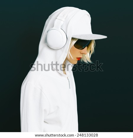 Sensual blonde DJ in sports white clothing listening to Music on black background. Urban fashion style - stock photo