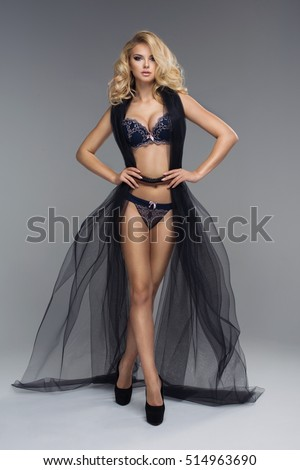 Sensual blonde lady posing in dark sexy lingerie