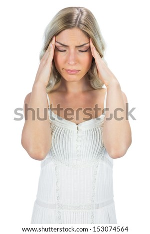 Sensual blonde on white background suffering while having a headache