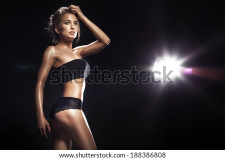 Sensual blonde woman posing in black sensual lingerie . Studio shot - stock photo