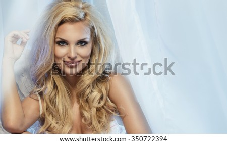 Sensual blonde woman posing in white sexy lingerie , looking at camera.  - stock photo