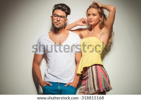 sensual blonde woman resting her hand on boyfriend while arranging her beautiful hair