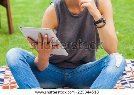 Sensual blonde woman sitting in park on blanket. She is using tablet pc. Outdoor photo. She looks relaxed