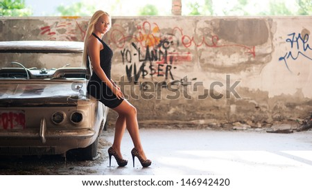 Sensual blonde woman standing near abandoned car. - stock photo