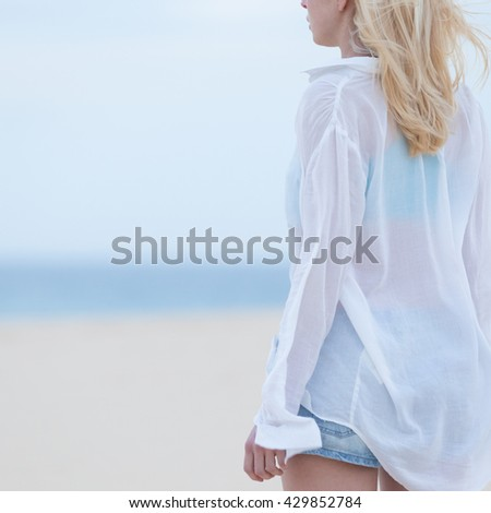 Sensual blonde woman wearing white loose casual shirt on vacations looking down sandy beach in dusk.