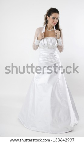 sensual bride stands right in white wedding dress and holding hands on the blouse with lace