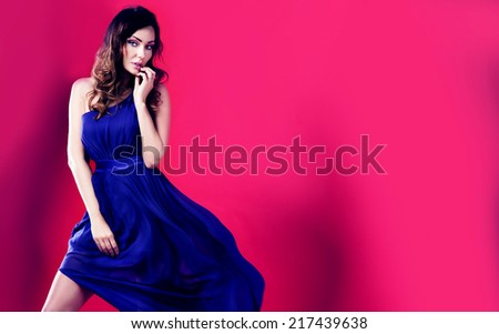 Sensual brunette beautiful woman posing in fluttering long dress. Pink background. Girl looking at camera - stock photo