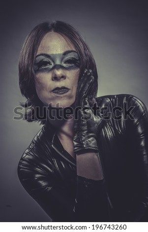 sensual, brunette girl dressed in black latex jumpsuit - stock photo