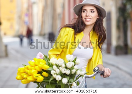 sensual brunette girl sitting on bicycle with some spring flowers in the basket