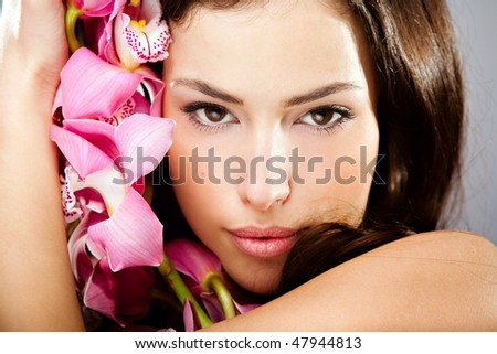 sensual brunette woman beauty portrait with orchid - stock photo