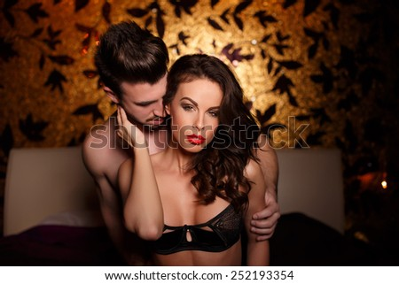 Sensual brunette woman in underwear with young lover, passionate couple foreplay - stock photo