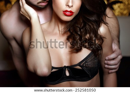 Sensual brunette woman in underwear with young lover, passionate couple foreplay closeup - stock photo