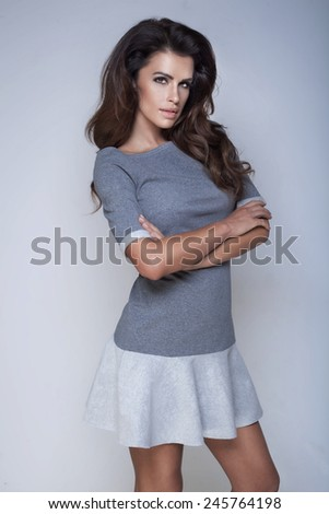 Sensual brunette woman posing in fashionable dress, looking at camera. - stock photo