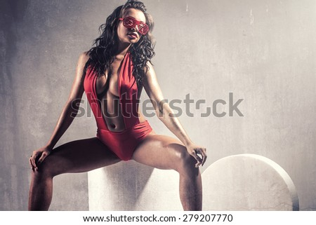 Sensual brunette woman posing in studio wearing red sexy beachwear and  sunglasses. Girl with long curly hair. - stock photo