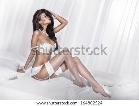 Sensual brunette woman posing in white sexy lingerie. Girl in bedroom. - stock photo