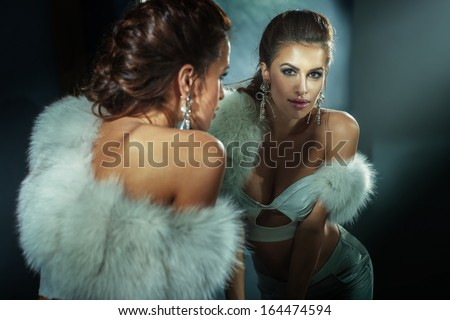 Sensual brunette woman posing wearing white fur, looking at the mirror. - stock photo