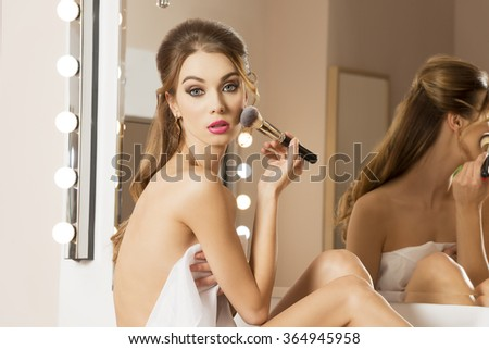 sensual brunette woman sitting in beauty salon in front of mirror with white towel on her naked body and elegant hairdo. She is applying blush on her cheek with make-up brush and looking in camera  - stock photo