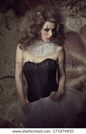 sensual brunette woman wearing like a dancer with sad clown make-up and crazy hair-style. Gothic fashion creative portrait  - stock photo