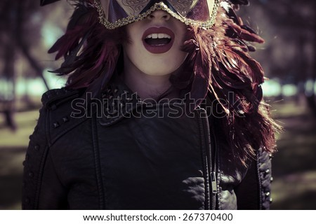 Sensual brunette woman with flowing hair and jacket with golden wings - stock photo