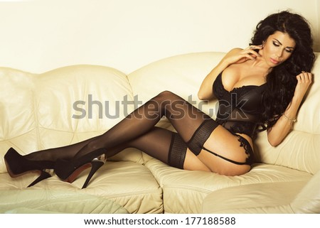 Sensual brunette woman with long hair lying in  bed, posing in sexy lingerie, looking at camera.