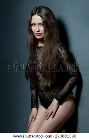 Sensual brunette woman with long hair posing in underwear, looking at camera. - stock photo