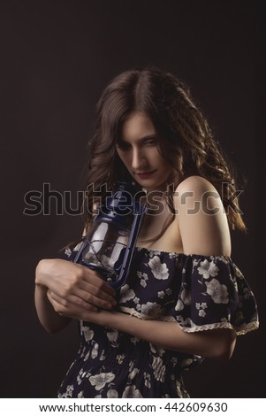 Sensual brunette woman with old kerosene lamp  in the shadows