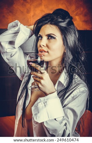 Sensual brunette young woman in  man's shirt  holding a glass of wine in the bedroom - stock photo