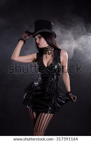 Sensual cabaret girl in fetish dress, black bead necklace, and tophat  - stock photo