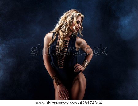 Sensual, confident, beautiful young blonde woman wearing black lingerie. Long curly hair, nice makeup. Head, face is turned sideways. Dark smoky Background - stock photo