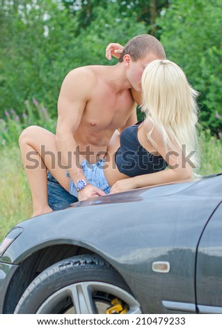 Sensual couple making love on the car's hood.