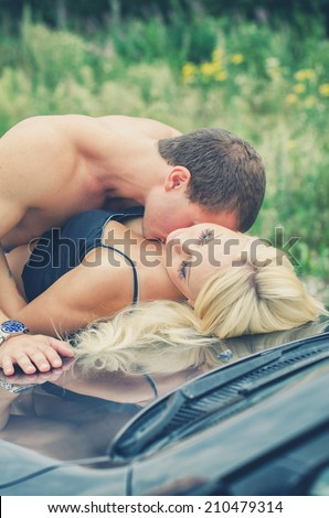 Sensual couple making love on the car's hood. - stock photo