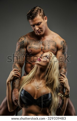 Sensual couple of blond female in black bra and shirtless tattooed male. Isolated on grey background.