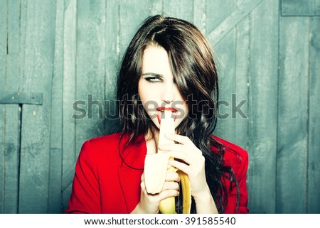 Sensual elegant emotional beautiful young woman with long lush brunette hair in stylish jacket holding and eating banana indoor on wooden background, horizontal picture - stock photo