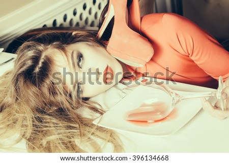 Sensual elegant glamour young drunk woman with beautiful hair lying on table with glass and poored red wine in plate after hangover with suide shoe, horizontal picture